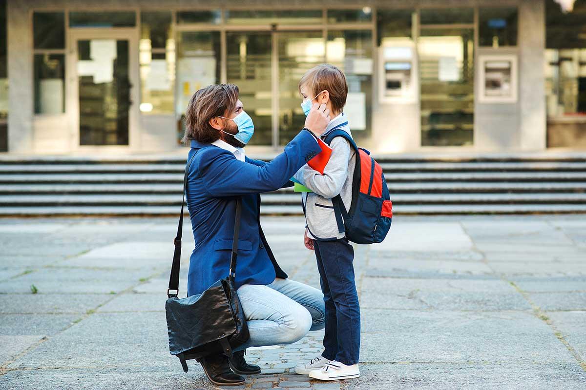 Schulkind und Mutter mit Maske vor Schulgebäude