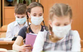 sitzende Schulkinder mit Maske